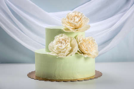 A beautiful home made wedding two-tiered cake decorated with beige roses.
