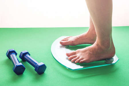 Female feet standing on electronic scales for weight control, dumbbells and measuring tape. The concept of sports training, slimming and weight loss