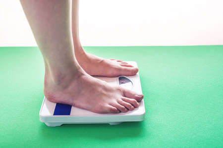 Female feet standing on mechanical scales for weight control. The concept of slimming and weight loss Stock fotó - 84752747