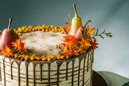 Beautiful large honey cake pour over the chocolate and decorated on top with pears and sea buckthorn on a wooden table. The concept of sweet autumn still life
