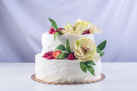 A beautiful home wedding two-tiered cake decorated with currants, strawberries and yellow flowers with green leaves in a rustic style. Festive berry dessert
