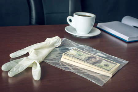 red handed: The glove and the bribe on the table in the form of dollar bills. Caught red-handed and evidence of the crime. The concept of corruption and bribery