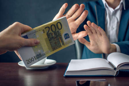 Man businessman in suit refuses to take the money by showing that he is not a grafter. A bribe in the form of Euro banknotes. The concept of corruption and bribery
