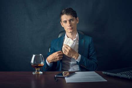 Hombre de negocios en traje pone dinero en su bolsillo. Un soborno en forma de billetes de un dólar. El concepto de corrupción y soborno. Foto de archivo