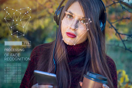 Biometric verification. Modern young woman with the phone. The concept of a new technology of face recognition on polygonal grid is constructed by the points of IT security and protection ID