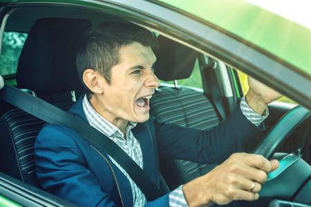 Boos man stuurprogramma schreeuwen in de auto. De ruzie en ontevredenheid onderweg.