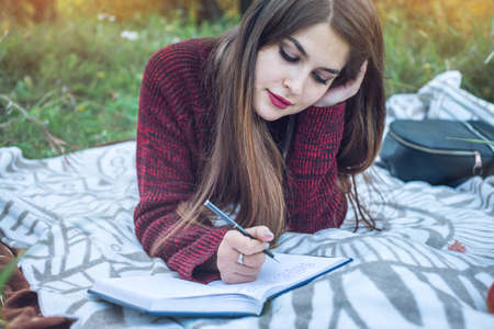 poems: Beautiful woman writer writing with pen autumn story in her notebook. The concept of education and working with nature Stock Photo