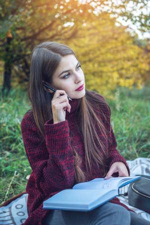아름 다운 여자 작가 그녀의 노트북에 펜가을 펜으로 작성합니다. 교육 및 자연과의 협력 개념