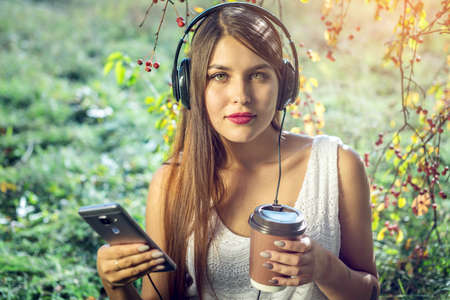 audio book: Attractive woman listening to music in your phone wearing headphones and holding a Cup of coffee in hand on a Sunny day in the Park. The concept of audiobooks and student education Stock Photo