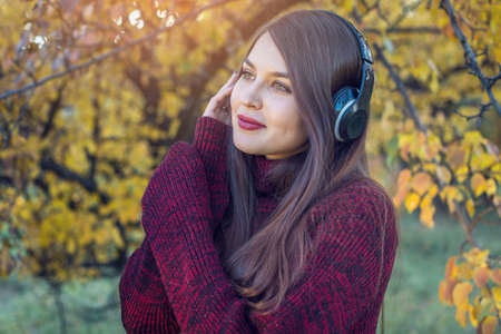 Beautiful woman in autumn Sunny Park standing listening to music with her headphones on the background of nature. The concept of good mood, favorite music, happy time. Stock Photo
