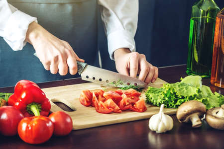 The chef in black apron cuts vegetables. The concept of eco-friendly products for cooking Banque d'images