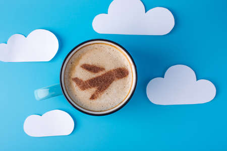 Cup of cappuccino with a picture of the plane on the foam. Blue sky background with paper clouds. The concept of travel and discover new places