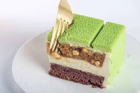 A piece of green cake with a filling of pears and cashews. Concept design pastry desserts