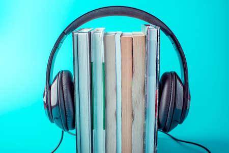 Auriculares negros con una pila de libros sobre un fondo azul. El concepto de audiolibros y educación moderna