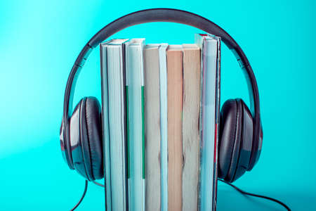 Black headphones with a stack of books on a blue background. The concept of audiobooks and modern education Archivio Fotografico