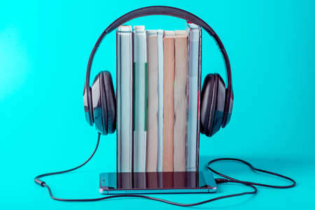 Phone with black headphones with a stack of books on a blue background. The concept of audiobooks and modern education Фото со стока