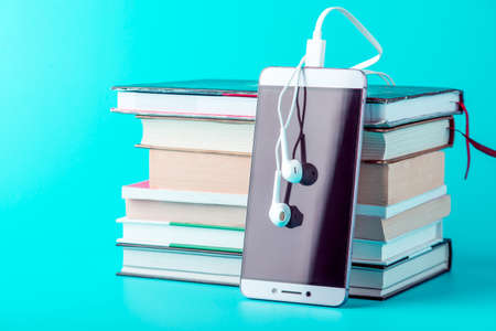Phone with white earphones next to a stack of books on a blue background. The concept of audiobooks and modern education