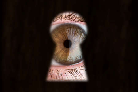 peephole: Womens brown eye looking through the keyhole. Stock Photo