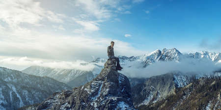 A young man in a sweater with phone in hand on the top of a snowy mountain far from civilization on a background of blue sky. The concept of activity and the availability of mobile connection