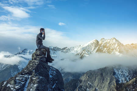 availability: A young man in a sweater with phone in hand on the top of a snowy mountain far from civilization on a background of blue sky. The concept of activity and the availability of mobile connection