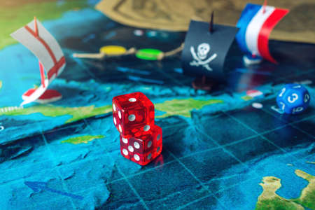 Red playing bones on the world map of the field handmade Board games with a pirate ship. The game of battleship. Stock Photo
