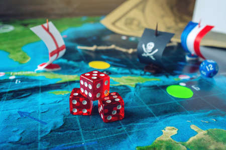 Red playing bones on the world map of the field handmade Board games with a pirate ship. The game of battleship. Banque d'images