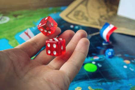 Ręka rzuca czerwone kostki na światowej mapie ręcznie gry planszowe ze statkiem pirackim. Gra w pancernik.