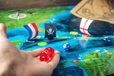 battleship: Hand throwing red dice on the world map of the playing field handmade Board games with a pirate ship. The game of battleship.