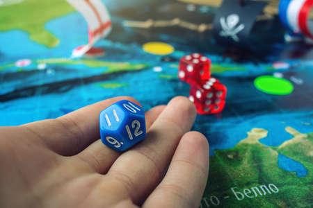 A mão rola os dados azuis no mapa do mundo dos jogos de mesa feitos a mão do campo de ação com um navio de pirata. O jogo do couraçado de batalha.