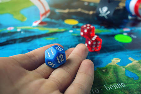 Hand rolls the blue dice on the world map of the playing field handmade Board games with a pirate ship. The game of battleship. Standard-Bild