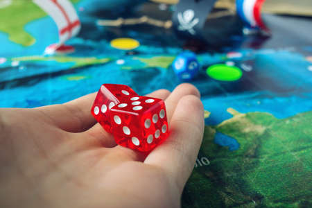 Hand throwing red dice on the world map of the playing field handmade Board games with a pirate ship. The game of battleship.