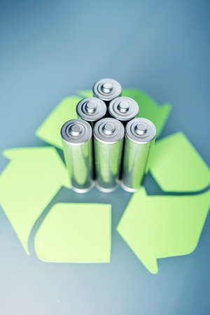 Used AA and proper disposal of toxic to the environment and soil batteries on a blue background. The concept of technologies of processing of harmful and recycling substances for ecological