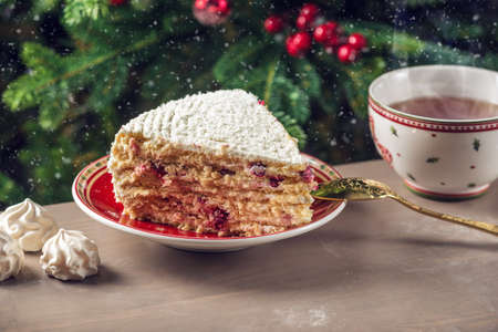 A piece of cranberry cake covered with white cream on plate on the background of the Christmas tree.