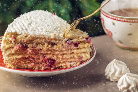 A piece of cranberry cake covered with white cream on plate on the background of the Christmas tree. Hand with Golden spoon breaks off part dessert.