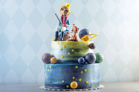 Big kids beautiful cake decorated in the form of the planet with the mastic figurines of the little Prince and the Fox. The concept of festive desserts for the birthday children Stok Fotoğraf