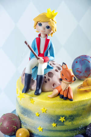 Big kids beautiful cake decorated in the form of the planet with the mastic figurines of the little Prince and the Fox. The concept of festive desserts for the birthday children Stock Photo