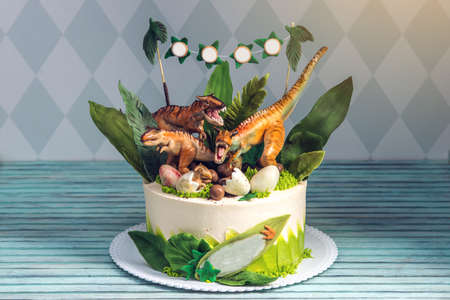 Childrens holiday white cake decorated with mastic figurines of dinosaurs in the Jurassic period jungle. Concept ideas desserts for kids Stock Photo