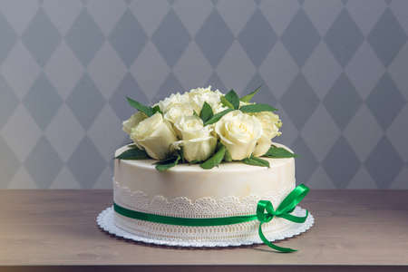Beautiful white wedding cake decorated with bouquet of flowers white roses. The concept of elegant holiday desserts