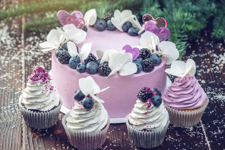Purple beautiful cake decorated with berries, blackberries and blueberries on top with cupcakes on the festive table. Concept delicate dessert holiday table