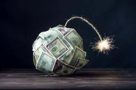 Big bomb of money hundred dollar bills with a burning wick. Little time before the explosion. The concept of financial crisis Standard-Bild