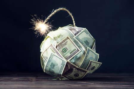 Grande bomba di denaro banconote da cento dollari con uno stoppino ardente. Poco tempo prima dell'esplosione. Il concetto di crisi finanziaria
