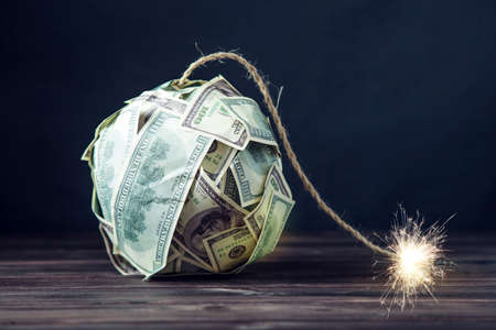 Big bomb of money hundred dollar bills with a burning wick. Little time before the explosion. The concept of financial crisis Banco de Imagens