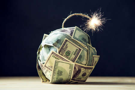 Bomba grande do dinheiro cem contas de dólar com um pavio ardente. Pouco tempo antes da explosão. O conceito de crise financeira