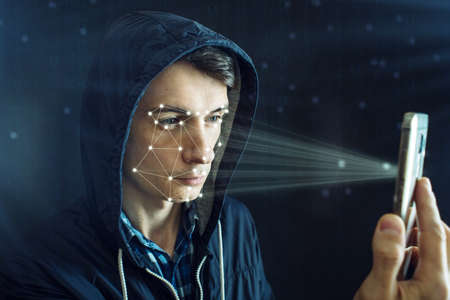 The hacker is trying to hack into the phone using the personal identification method of face recognition according to the polygonal mesh. The concept of modern technology