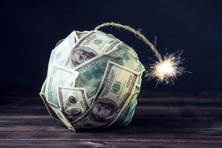Große Bombe des Geldes hundert Dollarscheine mit einem brennenden Docht. Kurz vor der Explosion. Das Konzept der Finanzkrise Standard-Bild - 92426800