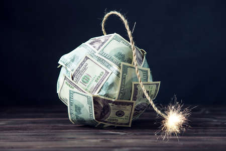 Big bomb of money hundred dollar bills with a burning wick. Little time before the explosion. The concept of financial crisis Foto de archivo