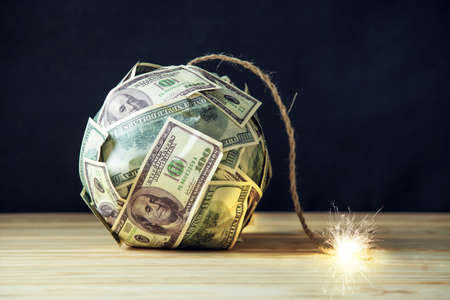 Big bomb of money hundred dollar bills with a burning wick. Little time before the explosion. The concept of financial crisis Stockfoto
