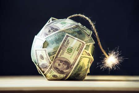 Wielka bomba pieniędzy sto dolarowych banknotów z płonącym knotem. Niewiele czasu przed wybuchem. Pojęcie kryzysu finansowego