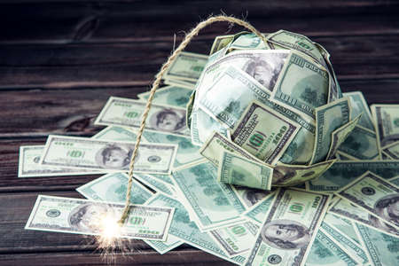 Big bomb of money hundred dollar bills with a burning wick. Little time before the explosion. The concept of financial crisis 版權商用圖片