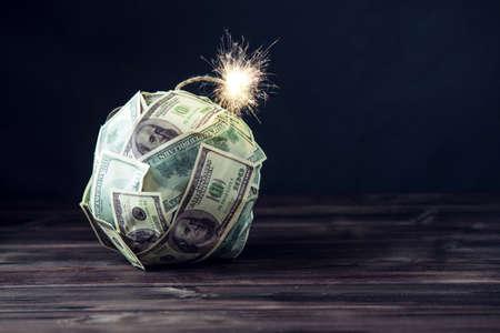 Grande bombe d'argent cent billets d'un dollar avec une mèche brûlante. Peu de temps avant l'explosion. Le concept de crise financière Banque d'images